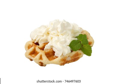 Belgian waffle topped with whipped cream and mint leaf isolated with clipping path