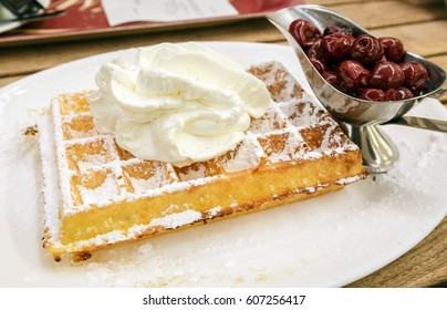Belgian waffle with wip cream topping and sweet cherries by side on white plate, famous traditional dessert of Belgium