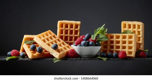 Belgian waffles with  blueberries, raspberries  and fresh mint a dark background.