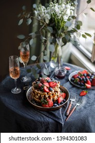 Belgian waffles for breakfast. Plate with waffles. Beautiful serve waffer cake with berries on a black rustic background  with champagne