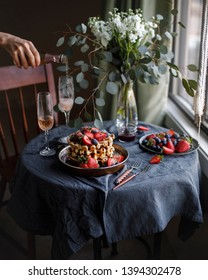 Belgian waffles for breakfast. Plate with waffles. Beautiful serve waffer cake with berries on a black rustic background  with champagne. Woman pours champagne