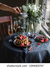 Belgian waffles for breakfast. Plate with waffles. Beautiful serve waffer cake with berries on a black rustic background  with champagne. Woman pours sugar powder