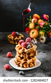 Belgian waffles for breakfast. Pours syrup from the spoon for dessert. Beautiful serve waffer cake with berries