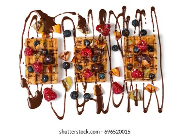 Belgian waffles with chocolate and berries on big white plate. Isolated.