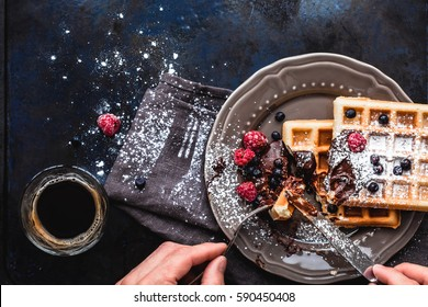 Belgian waffles with chocolate, berries and powdered sugar, a hand with a knife and fork, glass cup with coffee in the process of eating. Brussels breakfast.