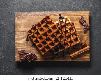 Belgian waffles with chocolate on wooden board.