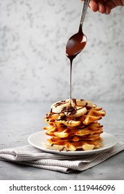 belgian waffles with chocolate sauce and banana on a gray concrete background