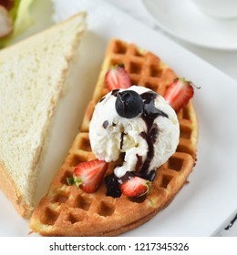 Belgian waffles with chocolate sauce, ice cream and strawberries and bluberries on a white plate close up.