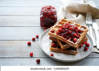 Belgian waffles  with cranberry sauce for breakfast. Light wooden background