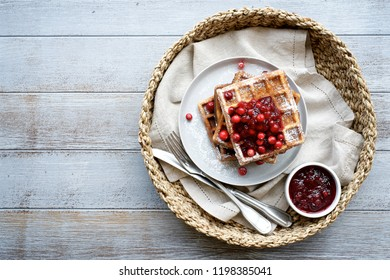 Belgian waffles  with cranberry sauce for breakfast. Light wooden background. Top view, empty space