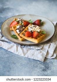 Belgian waffles with cream, chocolate and strawberries on a gray plate on a gray rustic background