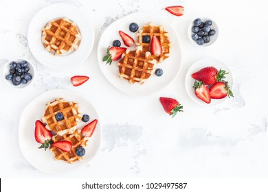 Belgian waffles with fresh strawberry and blueberry on white background. Flat lay, top view, copy space