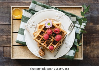 Belgian waffles with honey and raspberries for breakfast. Waffles decorated with flower, berries, granola and honey on wooden serving tray. Top view