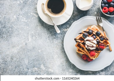 Belgian waffles with ice cream, berries and cup of coffee on concrete background. Top view with copy space for your text. Tasty breakfast