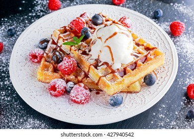 Belgian waffles with ice cream, chocolate sauce and fresh berries.