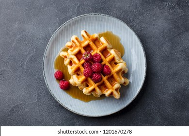 Belgian waffles with maple syrup and fresh raspberry. Grey slate background. Top view.