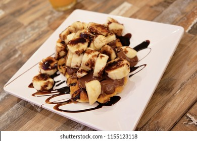 Belgian waffles on a white square plate stuffed with sliced bananas and hazelnut nutella paste, decorated with black chocolate sauce on a wooden table made from light and dark boards.