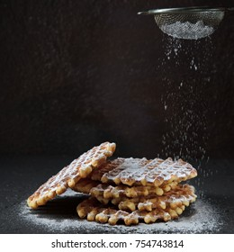 Belgian waffles with powdered sugar on black concrete background