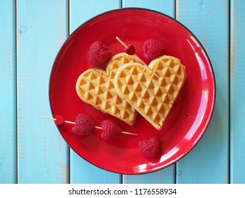 Belgian waffles in shape of heart with raspberries