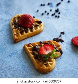 Belgian waffles in the shape of hearts with fresh strawberries and chocolate topping on blue table. Homemade healthy breakfast, selective focus