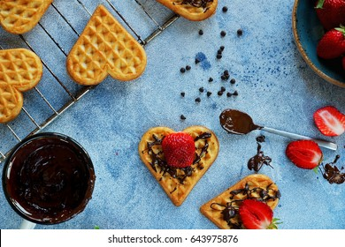 Belgian waffles in the shape of hearts with fresh strawberries and chocolate topping on blue table. Homemade healthy breakfast, top view