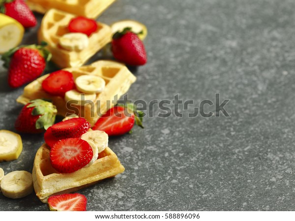 Belgian waffles with strawberries, banana and maple syrup on stone background with copy space