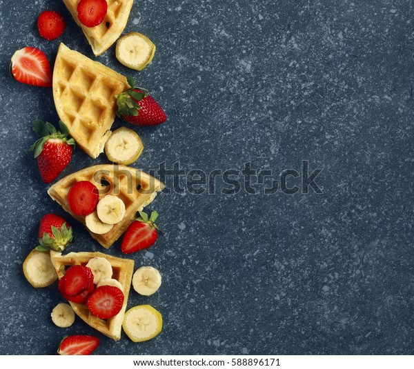 Belgian waffles with strawberries, banana and maple syrup