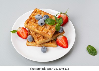 Belgian waffles with strawberries and blueberries for Breakfast.