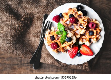Belgian waffles with strawberries, blueberries and syrup on wooden table.