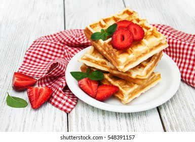 belgian waffles with strawberries and mint on a wooden table