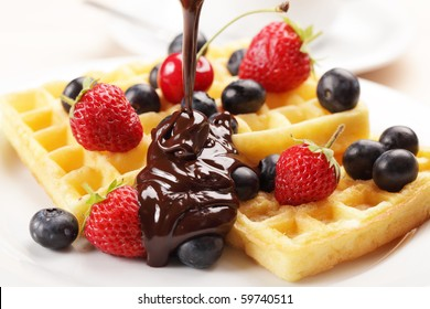 Belgian waffles with strawberry, cherry, blueberry, and chocolate sauce