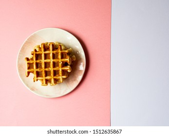 belgian waffles top view on color block background pink and white