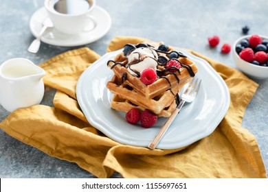Belgian waffles with vanilla ice cream and berries drizzled with chocolate and cup of coffee on the background. Selective focus