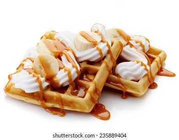 Belgian waffles with whipped cream, caramel sauce and bananas isolated on white background
