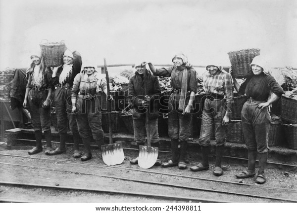 Belgian women coal miners dressed in trousers. They wear workers' clogs and headscarves, and tight belts that emphasize their waists. Between 1900-1920.