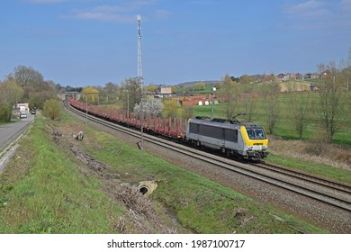 HENNUYÈRES, Belgium - April 08, 2021: LINEAS HLE 13 Yellow-White Electrical Locomotive with Empty Stake Car Freight Train in Green, Natural Environment under Blue Sky in Sunny Weather