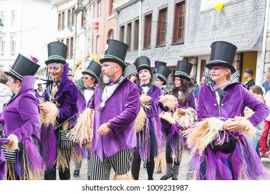 Belgium, August 20, 2017 Colorful's carnival parade of the world, traditional festival present with people dance in purple costume and put black bowler hat,funny and happy national culture and musical