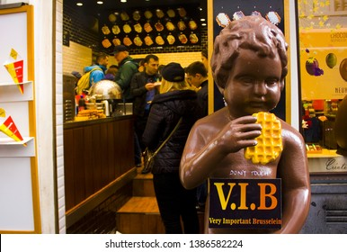 BELGIUM, BRUSSELS - May 1, 2019: Chocolate version of of the famous Manneken Pis statue in Brussels, holding the famous Belgian waffle in front of a waffle shop