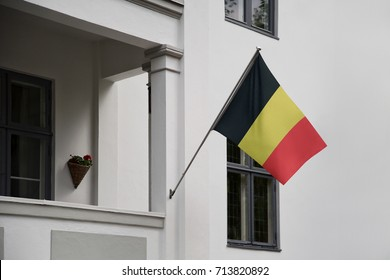 Belgium flag. Belgian flag displaying on a pole in front of the house. National flag of Belgium waving on a home hanging from a pole on a front door of a building.