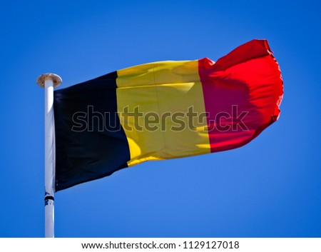 Belgium National Flag blowing in the wind showing tricolour.