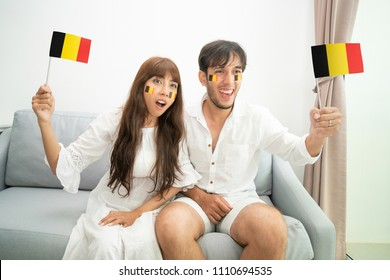 Belgium soccer fan cheering and watching world competitions on television in living room. International football cup event supporters.
