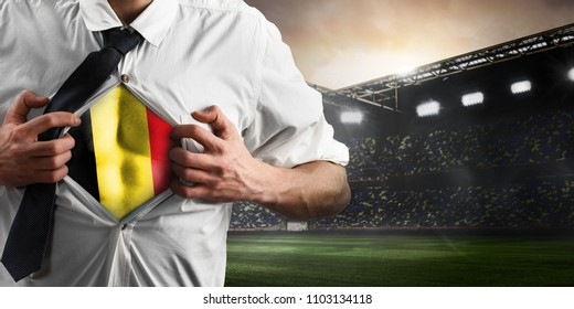 Belgium soccer or football supporter showing flag under his business shirt on stadium.