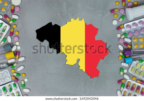 The Belgium State began research for treatment and medicine to combat the pandemic outbreak disease coronavirus. Medicine, pills, needles, syringes and Belgium map and flag on gray background.