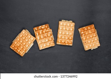 Belgium waffers on black board background. Top view of four fresh baked wafers.