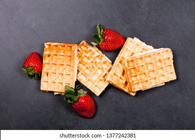 Belgium waffers and strawberries on black board background. Top view of four fresh baked wafers.