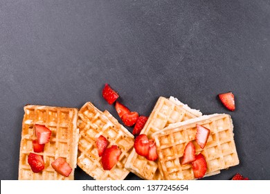 Belgium waffers and strawberries on black board background. Top view of four fresh baked wafers with copy space.
