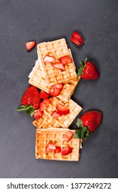 Belgium waffers with strawberries on black board background. Fresh baked wafers top view with copy space.