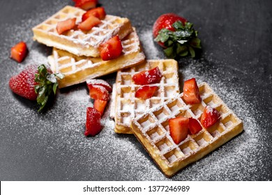 Belgium waffers with strawberries and sugar powder on black board background. Fresh baked wafers with copy space.