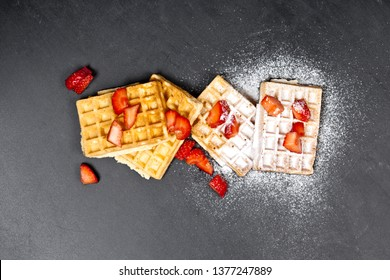 Belgium waffers with strawberries and sugar powder on black board background. Fresh baked wafers top view with copy space.