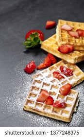 Belgium waffers with strawberries and sugar powder on black board background. Top view of fresh baked wafers with copy space.